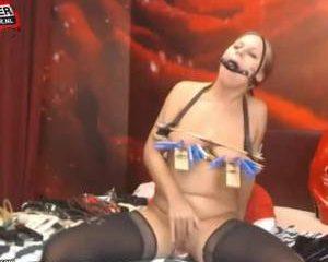 Met muizen klemmen op haar tieten neukt ze de dildo voor de webcam