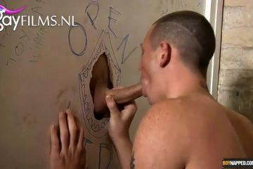 Hij pijpt de harde piemel door het gat van de muur