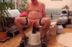 Met hoge hakken aan en nylon kousen neukt hij zijn anus met een dildo